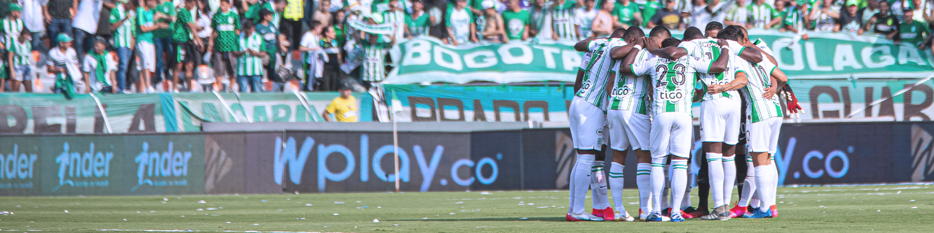 Players from Atlético Nacional, a major Colombian soccer club, stand together in the stadium with fans in the background