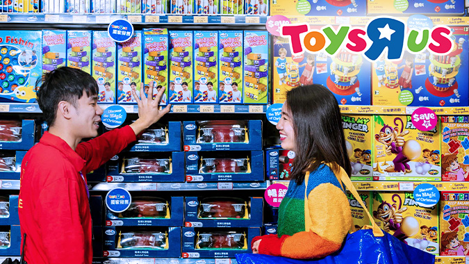 "Young woman being advised by Toys""R""Us Asia employee in front of a toy shelf in store"