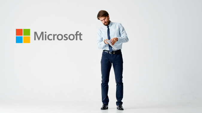 Businessman looking for something in his documents and Microsoft logo