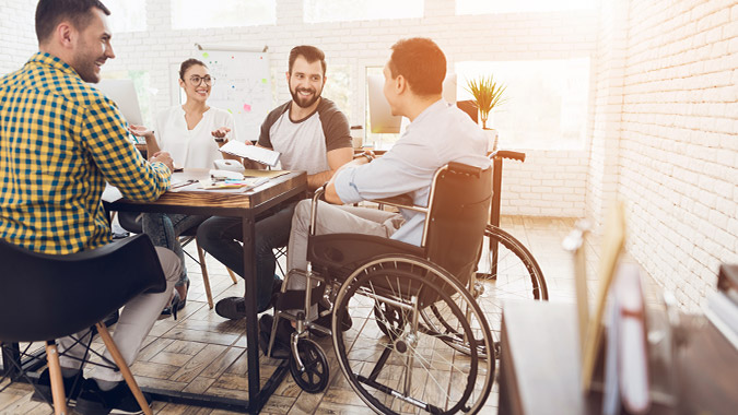 Man in a wheelchair communicates during in a business meeting